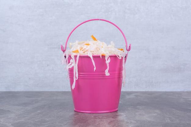 Leckeres hausgemachtes sauerkraut im rosa eimer.