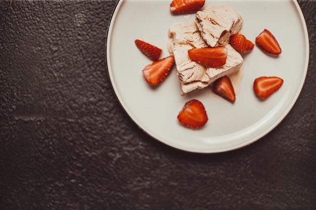Leckeres hausgemachtes vanilleeis mit erdbeere auf einem weißen teller auf dunklem hintergrund. sommer und süßes menükonzept.