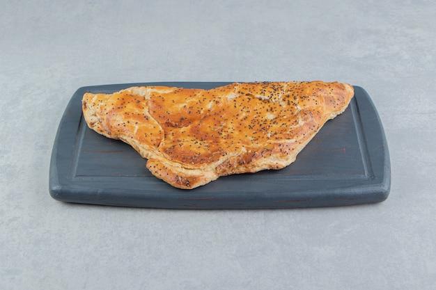 Leckeres käsegebäck auf dunklem brett.