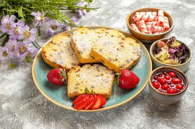 Leckeres kuchenstück der halben draufsicht mit erdbeeren auf kuchenkuchen der hellen oberfläche süß