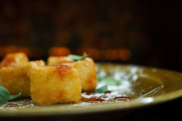 Leckeres leckeres süßes dessert, paniert, mit puderzucker bestäubt und mit minzblättern und erdbeermarmelade dekoriert. schöne kleine kuchenstücke. nahaufnahme