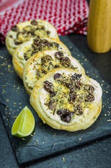 Leckeres libanesisches essen, mediterrane ricotta sfiha, gratinierte oliven mit käse, im hintergrund ein traditionelles libanesisches keffyeh.