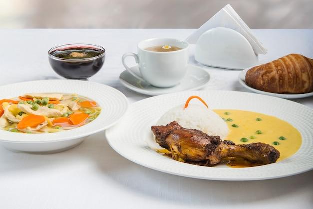 Leckeres mittagessen mit hähnchenkeule, reis, erbsen, suppe, dessert, tee und brot. serviert auf einem weißen tisch.