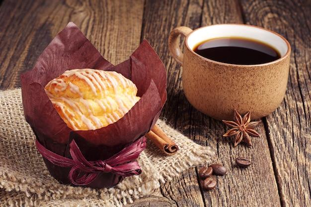 Leckeres muffin und kaffeetasse auf vintage holztisch