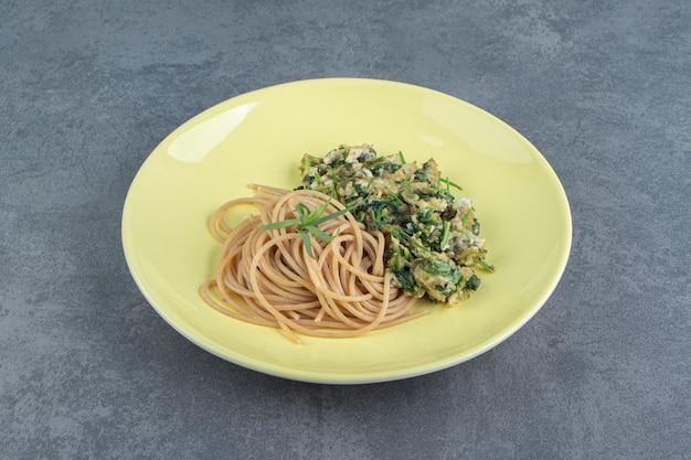 Leckeres omelett mit grüns und spaghetti auf gelbem teller.