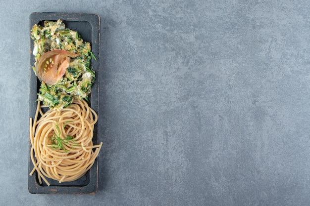 Leckeres omelett mit grüns und spaghetti auf schwarzem teller.