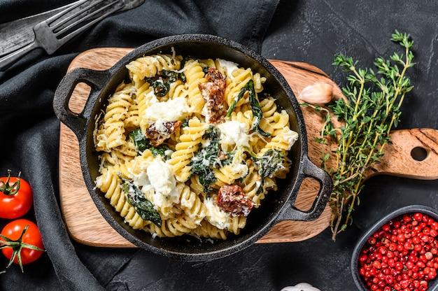 Leckeres pasta-fusilli-gericht mit cremiger spinatsauce und getrockneten tomaten. schwarzer hintergrund. draufsicht
