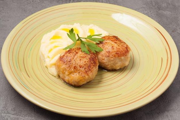 Leckeres püree mit butter und hühnerschnitzeln, verziert mit einem petersilienblatt