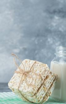 Leckeres quadratisches knäckebrot und eine flasche milch auf marmor.