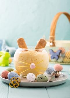 Leckeres reispudding-dessert, dekoriert von osterhasen mit bunten wachteleiern. feiertags-helthy nahrungsmittelkonzept mit kopienraum