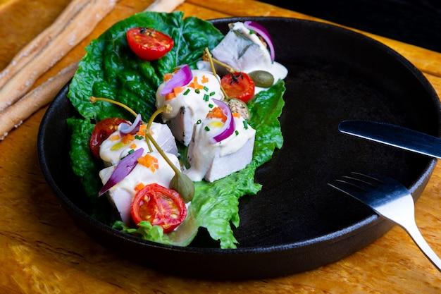 Leckeres restaurant gericht vitello tonato im restaurant. gesundes exklusives essen auf großer schwarzer platte nahaufnahme