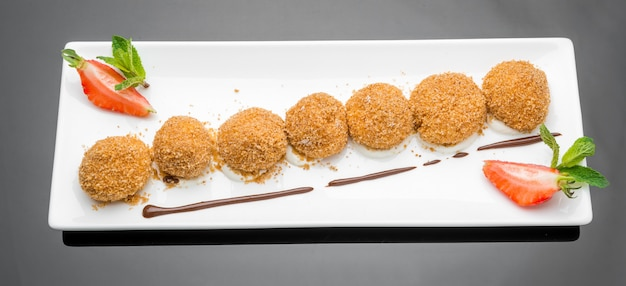 Leckeres restaurantdessert mit drei kugeln gebratenem eis mit schokolade und schlagsahne