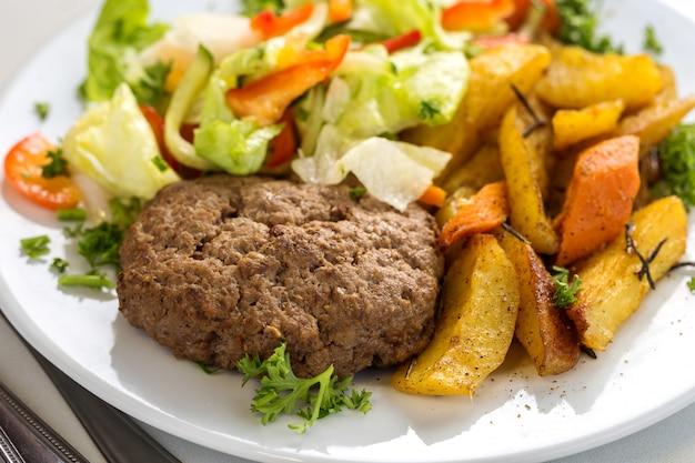 Leckeres rinderkotelett mit salat und kartoffelschnitzen