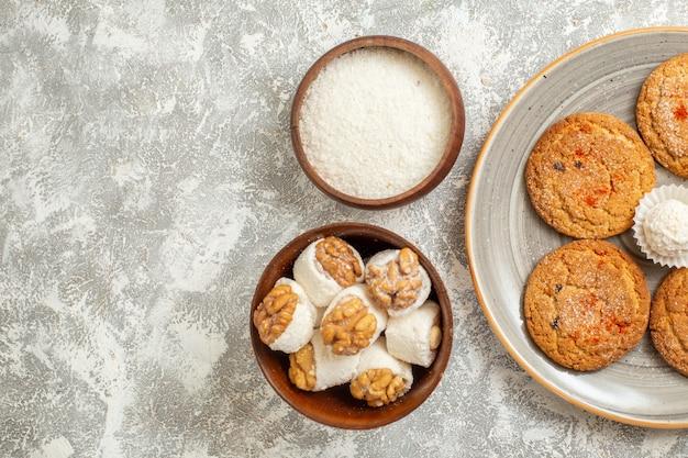 Leckeres sandplätzchen der draufsicht mit bonbons auf weißem hintergrund
