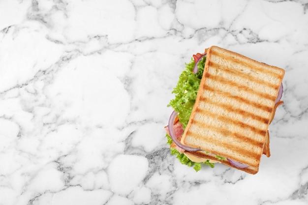 Leckeres sandwich mit geröstetem brot auf weißem marmortisch, draufsicht. platz für text