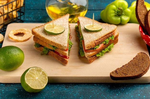 Leckeres sandwich mit grünen salattomaten und schinken auf blau