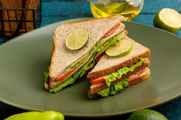 Leckeres sandwich mit grünen salattomaten und schinken in teller auf blau
