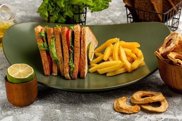 Leckeres sandwich mit grünen salattomaten und schinken in teller mit pommes frites