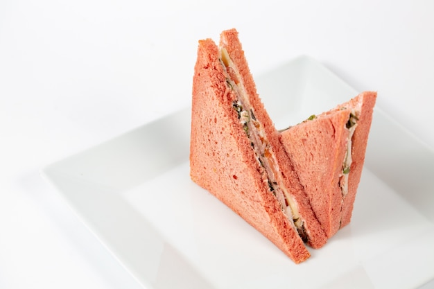 Leckeres sandwich mit rosa brot auf einem weißen teller