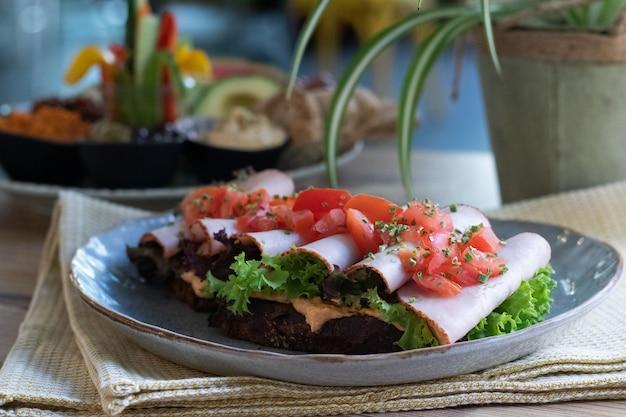 Leckeres sandwich mit schinken, salat, tomaten und frühlingszwiebeln