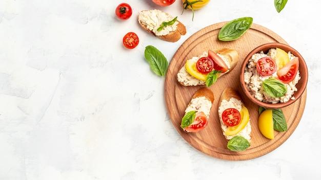 Leckeres sandwich mit tomaten, frischkäse und basilikumblättern auf weißem hintergrund. langes bannerformat. ansicht von oben.