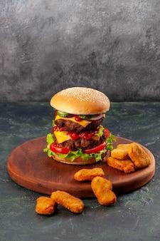 Leckeres sandwich und chicken nuggets auf braunem holzbrett auf eisfläche mit freiem platz