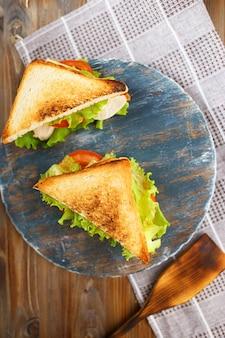 Leckeres sandwich zwei mit huhn, tomaten, kopfsalat, käse auf einer hölzernen platte auf einem dunklen hintergrund