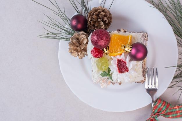 Leckeres stück kuchen mit tannenzapfen und ast des baumes