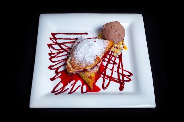 Leckeres süßes dessert. luftiger erdbeerstrudel mit puderzucker, erdbeermarmelade, dünnen haselnussstücken und einer portion schokoladeneis. schwarzer hintergrund