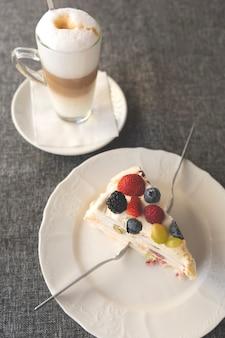 Leckeres süßes stück kuchen mit weißem zuckerguss und beeren auf einem teller mit gabeln zum teilen mit latte-kaffee auf grauem hintergrund