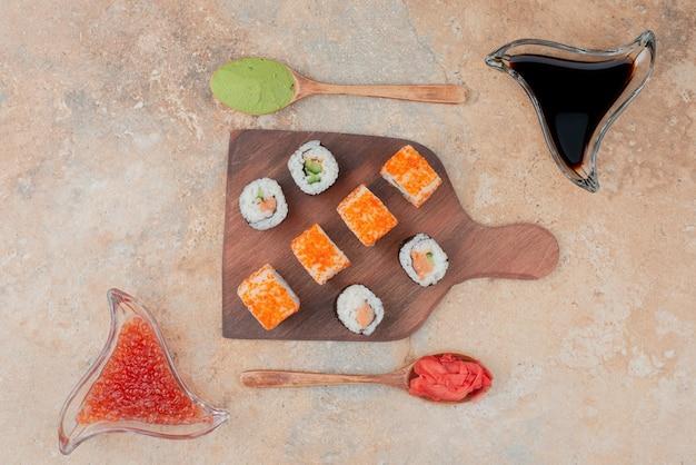 Leckeres sushi mit kaviar, ingwer und vasabi auf holzteller.