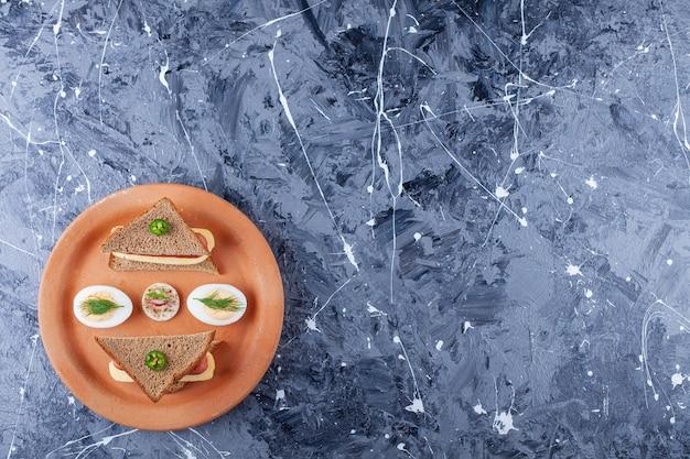 Leckeres toastbrot mit käse und eiern auf keramikplatte.