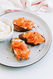 Leckeres toastsandwich mit lachs und käsecreme auf einem weißen teller.