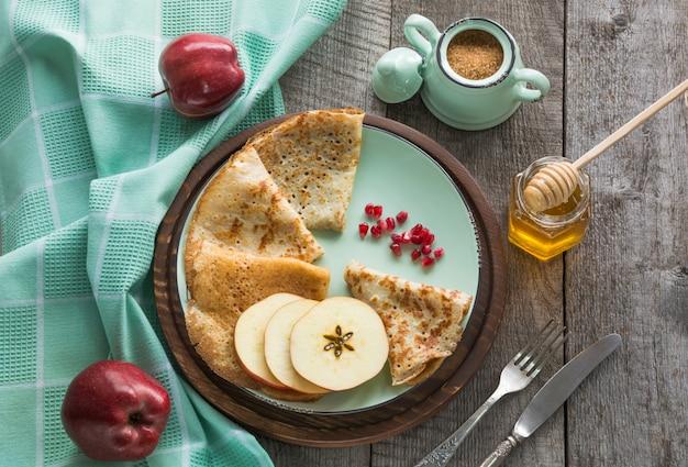 Leckeres traditionelles russisches frühstück von pfannkuchen mit honig auf teller. rustikaler stil.