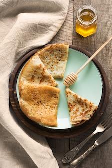 Leckeres traditionelles russisches frühstück von slapjack mit honig auf teller.