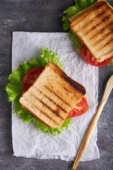Leckeres traditionelles vegetarisches sandwich mit tomaten und käse auf einem grauen steintisch vertikal