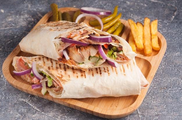 Leckeres türkisches shawarma mit hühnchen und gemüse mit zwiebeln