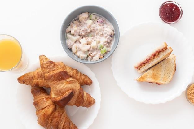 Leckeres und gesundes frühstück. croissants, orangensaft, ein sandwich mit marmelade und erdnussbutter, müsli mit joghurt, banane und apfel