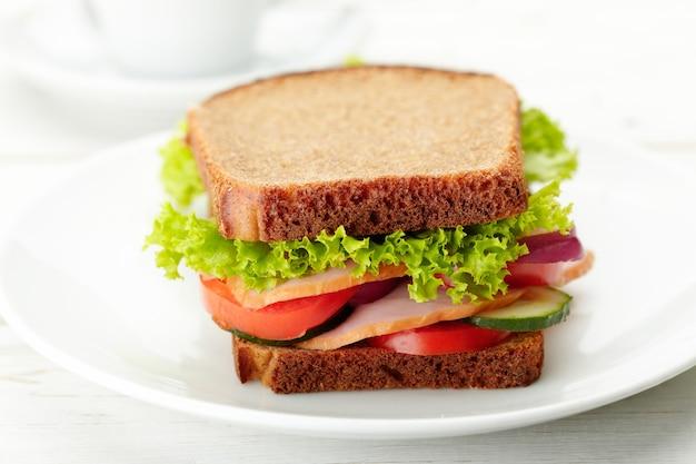 Leckeres und gesundes sandwich mit schinken, salat, tomate, zwiebeln und gurke auf einem teller