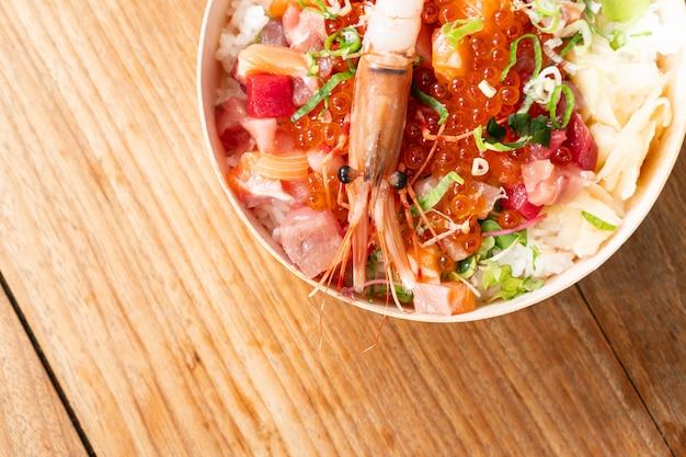 Leckeres und köstliches japanisches chirashi essen auf holztischhintergrund, gesundes essen und essen gut konzept. essen zum mitnehmen. draufsicht, kopierraum