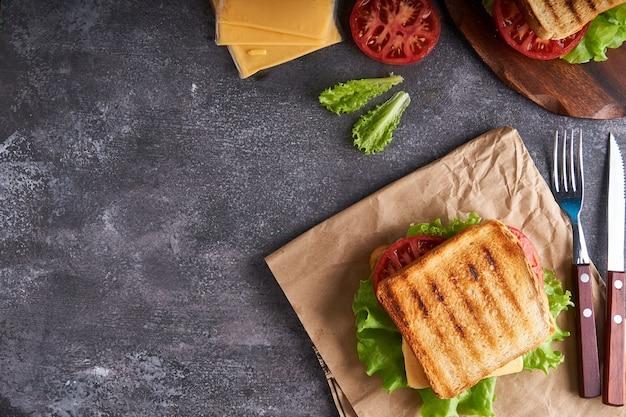 Leckeres vegetarisches sandwich mit tomaten und käse auf einem grauen steintisch copyspace draufsicht
