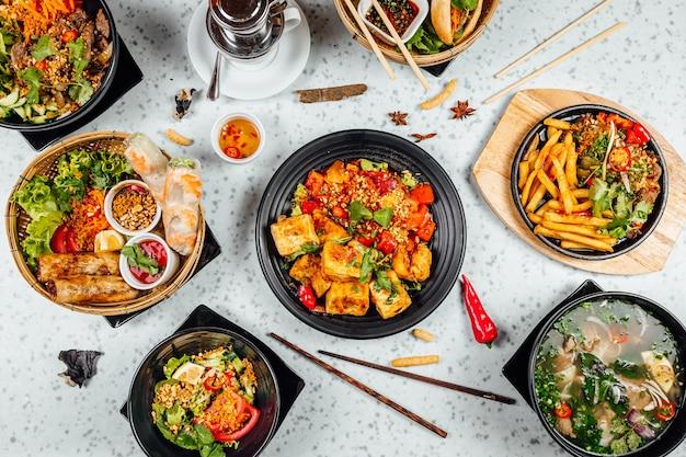 Leckeres vietnamesisches essen einschließlich pho ga, nudeln, frühlingsrollen auf weißem tisch