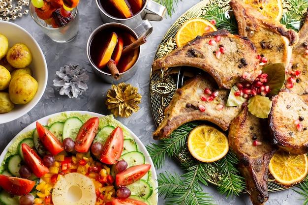 Leckeres weihnachtsessen mit gebratenem fleischsteak, weihnachtskranzsalat, ofenkartoffel, gegrilltem gemüse, preiselbeersoße.