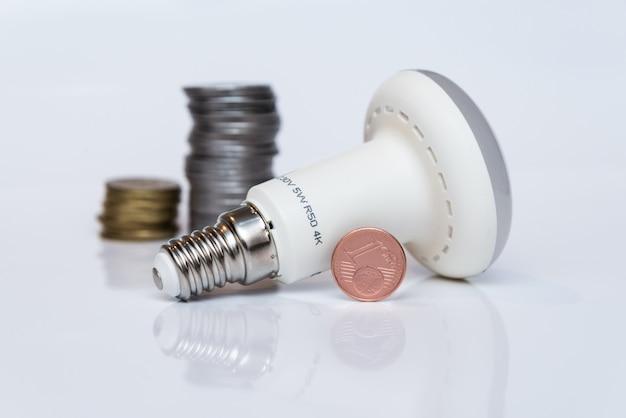 Led-economy-lampe steht auf einer weißen fläche neben münzen