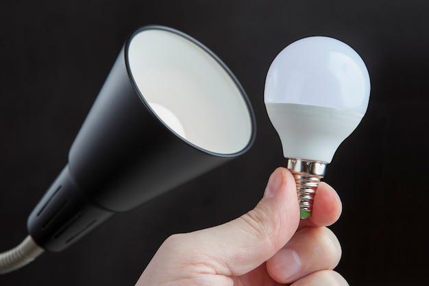 Led elektrische glühbirne in der menschlichen hand nahe lampenschirm stehlampe, gegen dunkelheit.