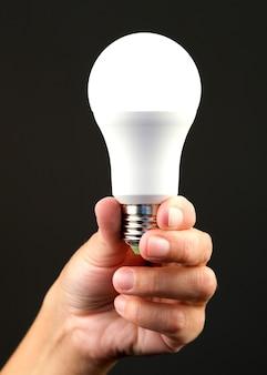 Led-energiesparlampe in der hand einer person geführt. konzept der modernen wirtschaftlichen beleuchtung.