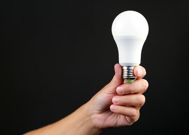 Led-energiesparlampe in der hand einer person geführt.