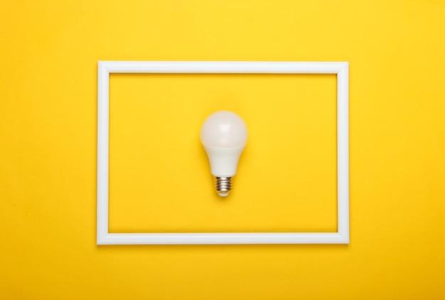 Led-glühbirne auf gelber oberfläche mit weißem rahmen