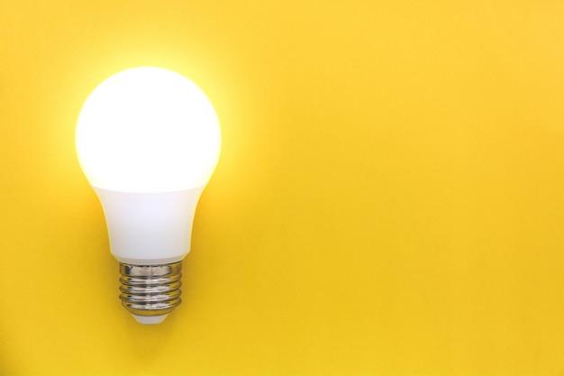Led-glühlampe auf gelbem hintergrund, konzept von ideen, kreativität, innovation oder einsparungsenergie, kopienraum, draufsicht, ebenenlage