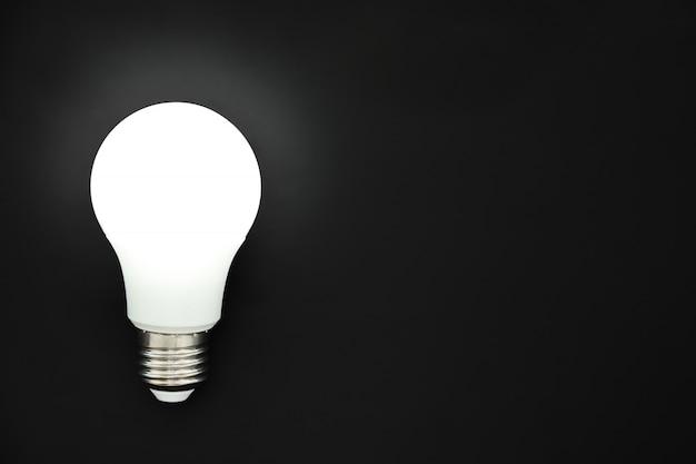 Led-glühlampe auf schwarzem hintergrund, konzept von ideen, kreativität, innovation oder einsparungsenergie, kopienraum, draufsicht, ebenenlage